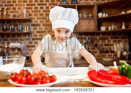 Little Girl Making Pizza Dough With Pizza Ingredients On Foreground