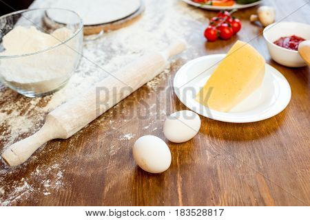 different pizza ingredients eggs and cheese on wooden tabletop poster