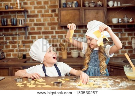 Excited Kids Playing With Dough For Shaped Cookies In Kitchen