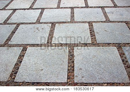 Layout of dressed rectangular grey granular granite stone slabs on pavement