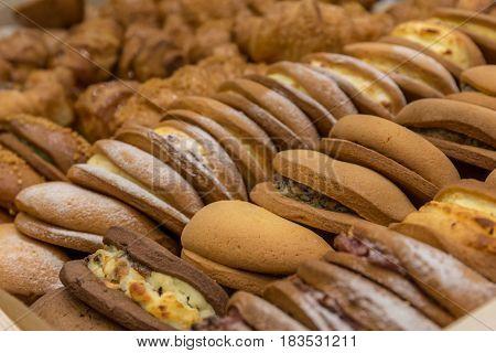 Bakery background, many different snacks with filling on market shelf
