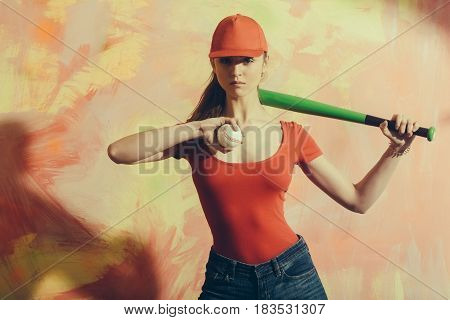 Pretty girl or sexy baseball player with blond hair in red cap tshirt and blue jeans standing with green bat and ball on abstract yellow and pink wall