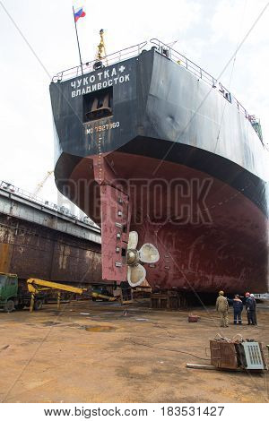 Slavynka Russia - April 21th 2017: Port Slavynka ship-repair factory sea ship-repair dock with a vessel in it experts discuss repair of the screw of a vessel.