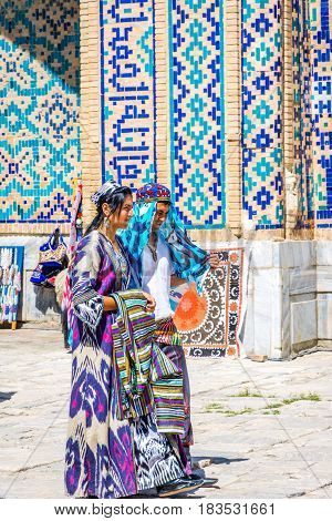 SAMARKAND UZBEKISTAN - AUGUST 28: Bride and groom in traditional Uzbek wedding clothes - colorful and patterns in Samarkand Registan. August 2016