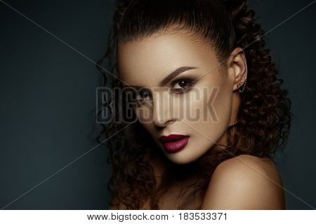 Beautiful face of a fashion model with black eyes.Curly hair. Pink lips. Studio portrait.