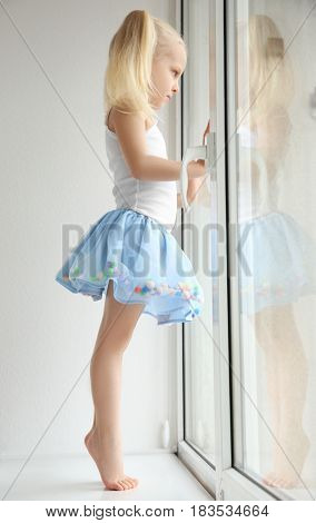 Cute little girl standing on windowsill