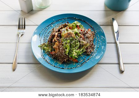 Restaurant food on white wood. Warm meat salad with sesame, vegetables and lettuce on blue plate. Appetizing dish served with soy sauce, dinner meal. Decorated healthy meal for gourmet