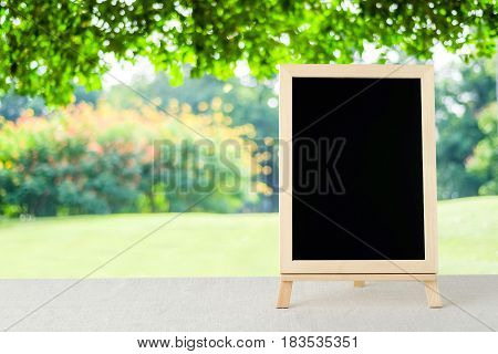 Blank chalkboard standing on sack tablecloth over blur tree background space for text mock up product display montage
