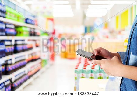 Hand holding smart phone over blur supermarket store background online shopping digitalmarketing e-commerce business and technology background template