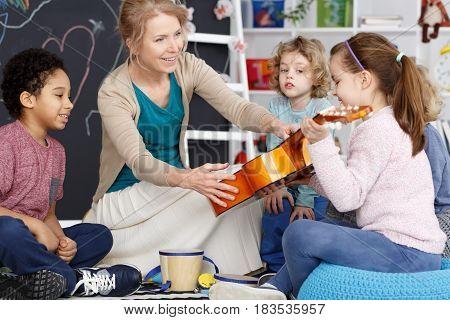 Little preschool girl holding teacher's guitar on music lesson