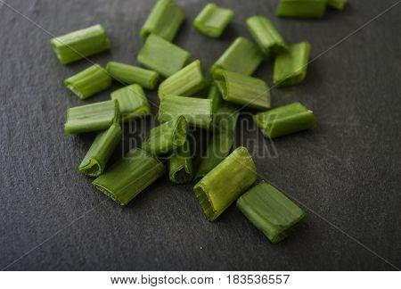 chopped green onions on dark onion close up