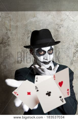 Bluff, Scary evil clown playing with poker cards