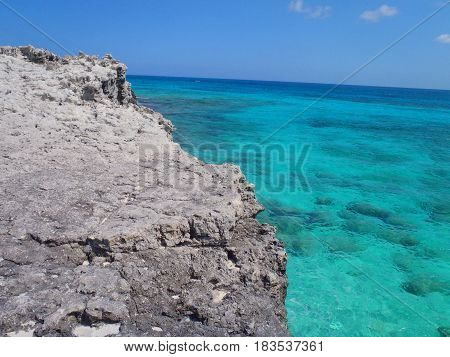 Crystal clear coral filled ocean seen from a cliff