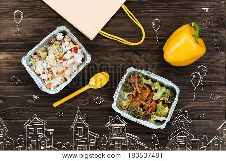 Take away. Top view of cooked rice and vegetables near the package that is lying nearby
