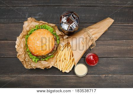 Fast food dish top view. Meat burger, potato chips and glass of cola drink with ice on wood. Takeaway composition.