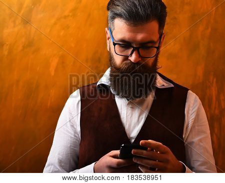Bearded man long beard. Brutal caucasian unshaven serious hipster with glasses and moustache surfing internet on cell phone wearing white shirt and suede waistcoat on brown studio background