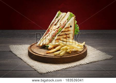 Fast food meals at sandwich bar. Chicken and vegetables sandwich and french fries, potato chips on wooden board