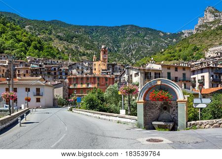 View of narrow road, small alpine town and mountains on background in France.