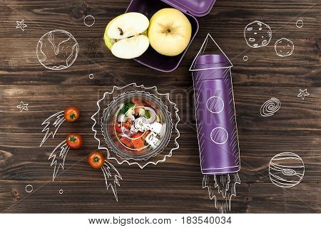 Only fresh products. Top view of greek salad bowl standing on the table near thermos and apples
