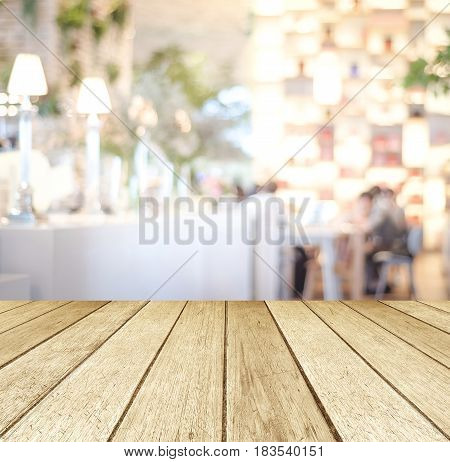 Empty perspective wood tabletop over blur restaurant with bokeh light background food and product display montage background