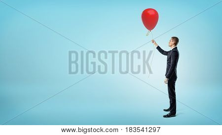 A businessman standing in side view on blue background and holding a red air balloon. Business and charity. Gifts and presents. Promotions.