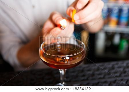 Barman's hands in bar interior making alcohol flaming cocktail. Professional bartender at work in bar mixing drink with burning fire. Party time in night club