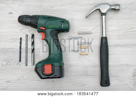 A hammer, a cordless drill with a set of bits, several screw bolts, dowels and plugs on white wooden background. Renovation works. Do it yourself. Tool set.