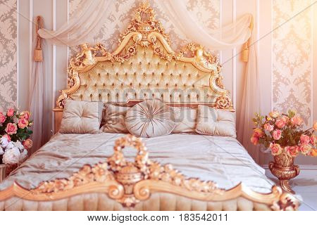 Luxury bedroom in light colors with golden furniture details. Big comfortable double royal bed in elegant classic interior. Toned picture.