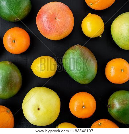 Fresh citrus and mango fruits on black background. Flat lay, top view. Summer background