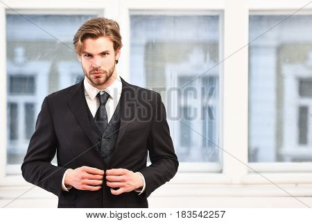 Businessman in elegant black suit in office. Confidence and charisma concept copy space