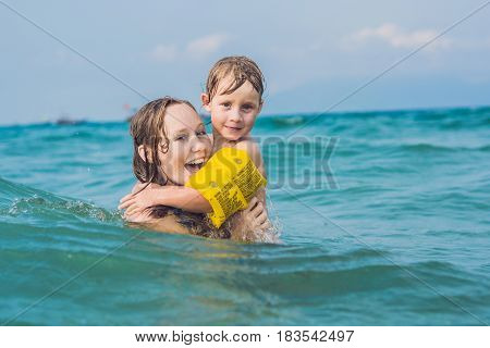 Young Mother Swimming And Playing With Male Child Boy In Sea Or Ocean Water Sunny Day Outdoor On Nat