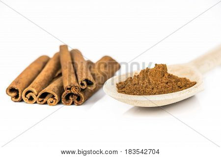 Cinnamon sticks and wooden spoon with ground cinnamon powder on white background