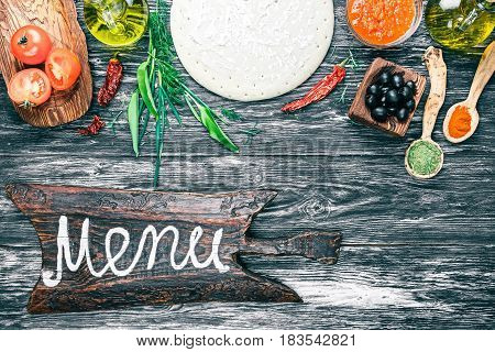 Pizza ingredients - round dough base, fresh tomatoes, sauce, olive oil, green herbs and spices on background of black textured wood. Rustic signboard 'Menu'. Top view