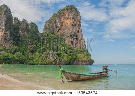 Traditional long tail boat on Railay Beach with mountain and blue sky background, Krabi, Thailand.