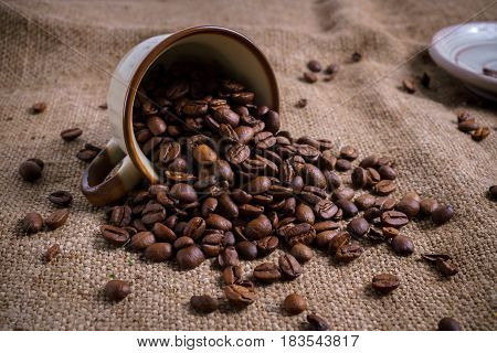White Cup full of roasted coffee beans on rustic old cloth.