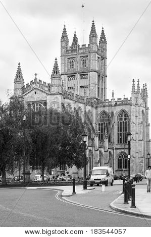 Bath Somerset United Kingdom - June 19 2006: The Abbey Church of Saint Peter and Saint Paul also known as Bath Abbey in Bath. It is an Anglican parish church and a former Benedictine monastery. Tourists walking and resting on the bench. Black and white.