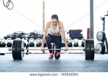 Beautiful young fit woman in gym lifting heavy barbell, flexing muscles