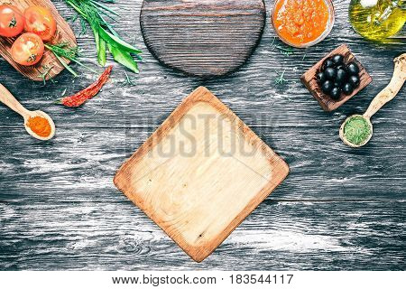 Vegetarian ingredients of italian cuisine - fresh tomatoes, red sauce, olive oil, green herbs and spices on background of black textured wood. Wooden plate as frame. Top view