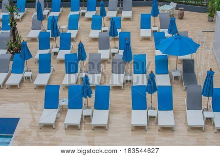 Vacation Concept : Daybeds and umbrellas on wooden floor outside the hotel in rainy day.