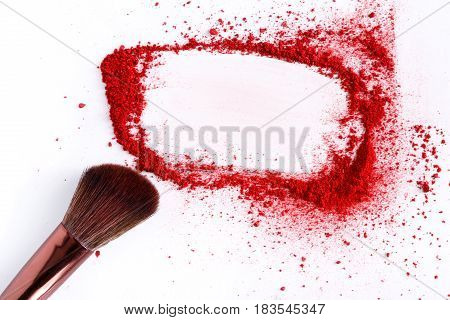 Makeup brush frame background with blush of red tone sprinkled on white. Make up and female cosmetics background