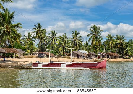 Ambatozavavy Nosy Be Madagascar - December 19 2015: Traditional wood pirogue and a modern boat with outrigger on the shore of the fishing village on the Nosy Be island Madagascar.