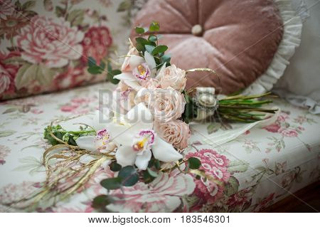 beautiful pink bouquet of roses lying on the sofa