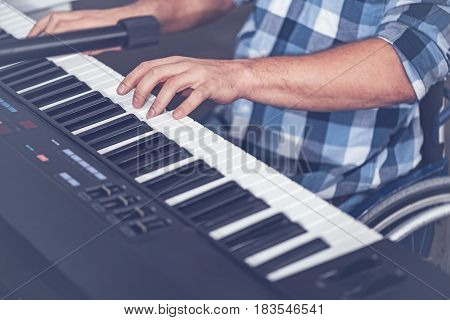 Enjoying every note. Skilled young inspired handicap sitting in the wheelchair in the studio and enjoying hobby while playing the musical keyboard