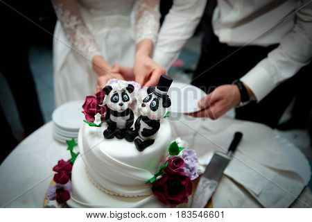 the bride and groom cut the white wedding cake with animal figures