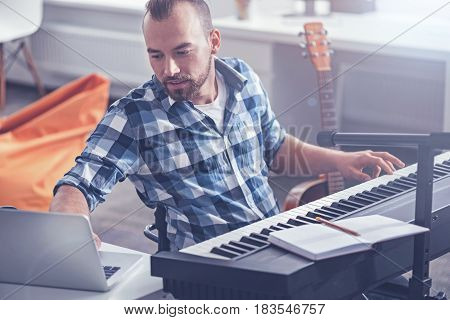 Recording my first song. Creative skilled smart disabled sitting in the wheelchair in the studio and enjoying musical therapy while playing the musical keyboard and using laptop for recording