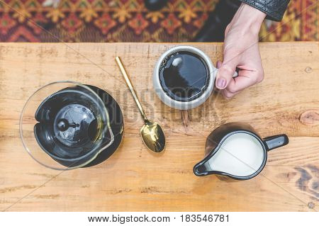View from above of woman holding coffee cup on table with creamer, french press, and gold spoon.