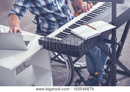 Practicing recording my songs. Skilled gifted young invalid sitting in the wheelchair in the studio and enjoying musical therapy while playing the musical keyboard and using laptop for recording