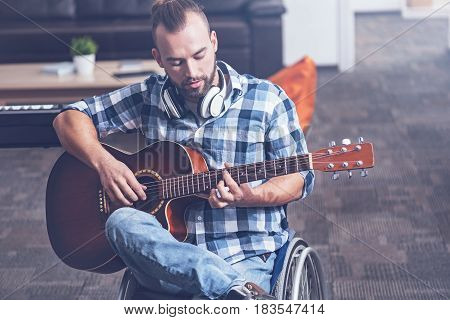 Enjoying every tune. Concentrated gifted positive invalid sitting on the wheelchair in the studio and practicing playing guitar while enjoying free time