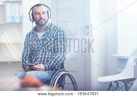 Visualizing my happy future. Young optimistic bearded man sitting on the wheelchair indoors and using modern gadget and earphones while enjoying music