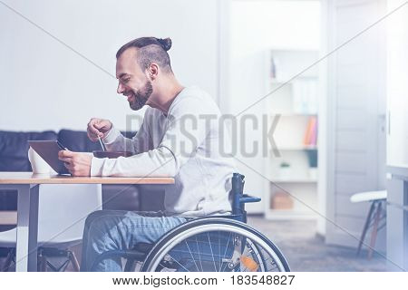 Begin the day with healthy breakfast. Smiling amused bearded handicap sitting on the wheelchair at home and enjoying breakfast while using tablet